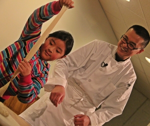 Ava Wu hones her noodle crafting skills as her dad, Chef Gene Wu looks on.
