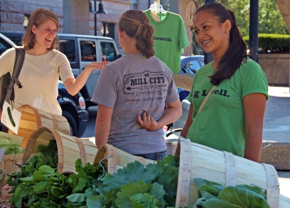 Alana Kelley (center) and Carolina Espinosa-Gil (right) work the Mill City Grows tent at the Lowell Farmers Market.