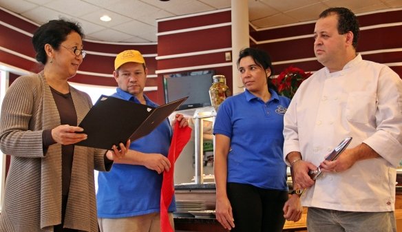Theresa Park reads a citation from Mayor Murphy and the City Council to the owners and staff of Cafe Pastiche.